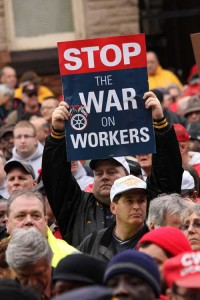 """one person holding sign that says """"stop the war on workers"""" among crowd at the demonstration"""