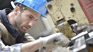 Industrial worker working on machine in factory 360x204