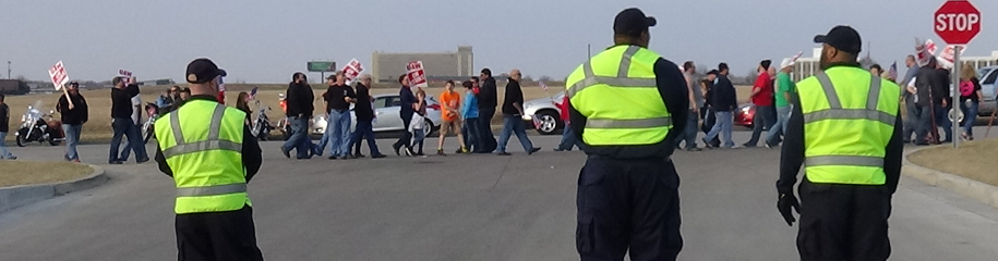 Strike security officers standing at entrance of plant with picketing union members on strike